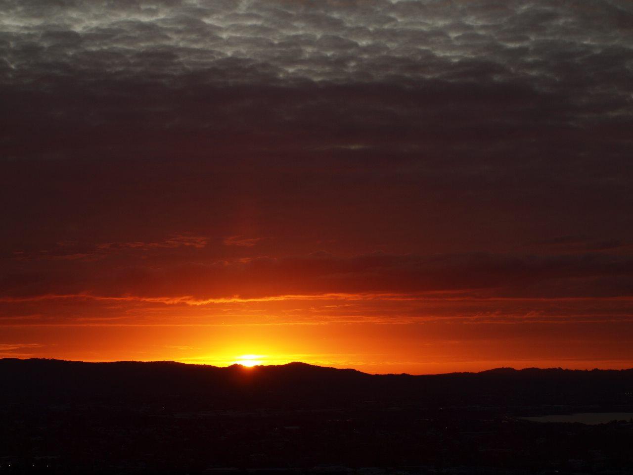 マウント・イーデンから。ワイタケレの山に夕日が落ちる